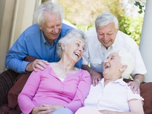 Group of senior friends sitting on garden seat laughing